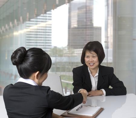 entrevista: Retrato de la empresaria asi�tica apret�n de manos con su colega