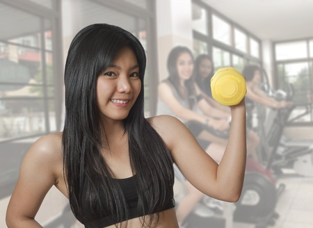 Young Asian woman working out with weights photo