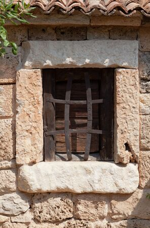 rejas de hierro: Ventana de madera histórico con barras de hierro en la pared de ladrillo de piedra Foto de archivo