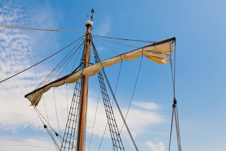 furled: mast sailing ship with ropes and furled the sail