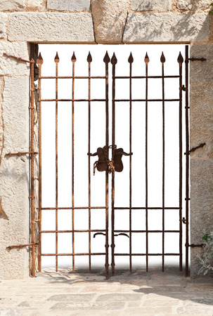 orchestrate: old wrought iron gate in a stone wall