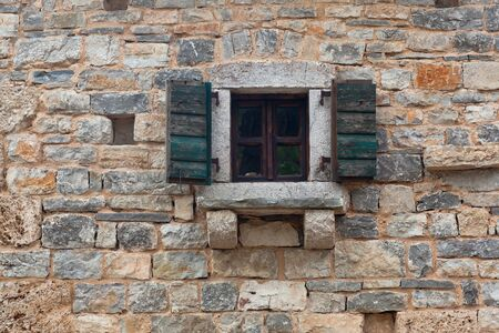 Old wooden window with closed shutters in a brick stonewall