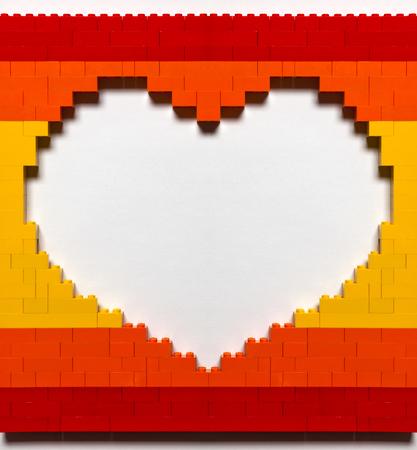 Loch in der Form des Herzens aus roten, orange und gelben Ziegeln mit Schatten auf weißem Hintergrund