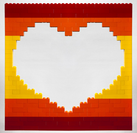 hole in the shape of heart from red, orange and yellow bricks on a white background