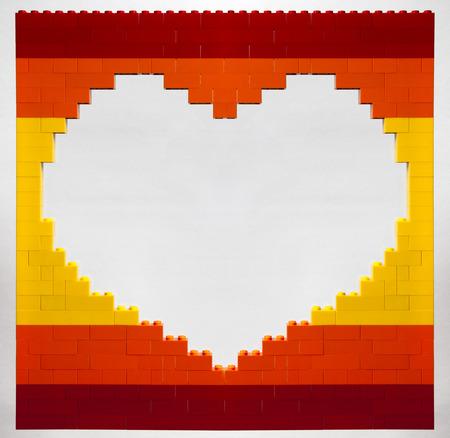 Loch in der Form des Herzens aus roten, orange und gelben Ziegeln auf weißem Hintergrund