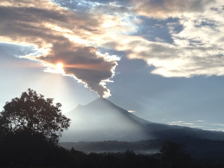 active volcano: In Mid-Sunrise with an active volcano sending a long ashes cloud hiding the sun that is light showering the half of the landscape.