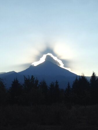 Sunrise behind the volcano casting a luminous volcano activity and shading the forest. Banco de Imagens