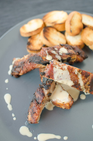 Spareribs on grill with dip, toasted baguette photo