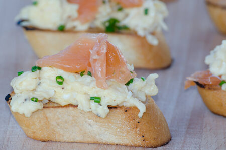 Toast with smoked salmon with scrambled eggs on wood plate photo