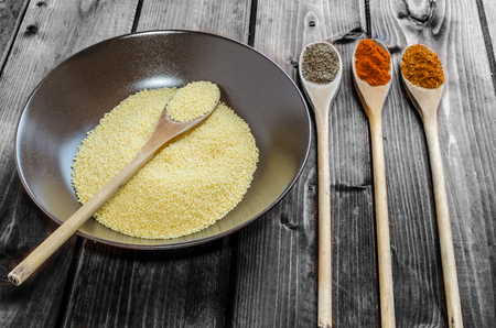 Spice on spoon with bowl of couscous on wood photo
