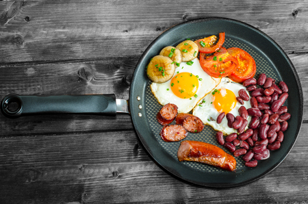 English breakfast on frying pan and wood table photo