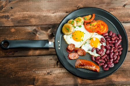 breakfast food: English breakfast on frying pan and wood table