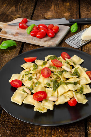 Home made ravioli with basil pesto, cherry tomato photo