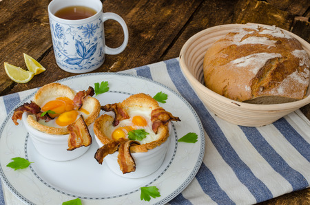 Muffins with eggs and bacon with black tea and lemon photo
