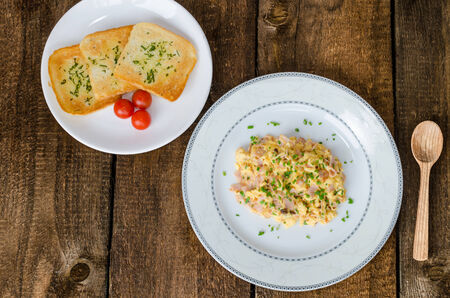 Scrambled eggs with chive and bacon, toast with herbs on wood table photo