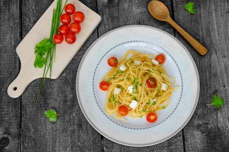 Spaghetti with cherry tomatoes and mozzarella, olive oil photo