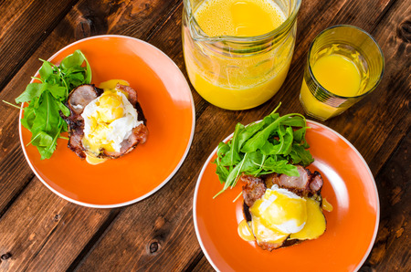 English muffin with bacon, egg benedict with hollandaise sauce and arugula salad, fresh orange juice photo