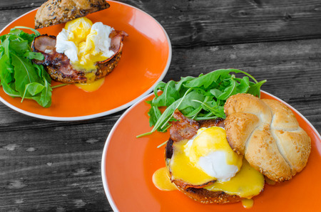English muffin with bacon, egg benedict with hollandaise sauce and arugula salad photo