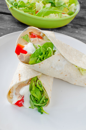 Tortilla chicken with salad, paprika and arugula salad photo