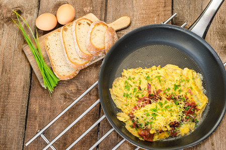 Omelet with bacon and cheese, home bread and chive on top, on frying pan photo