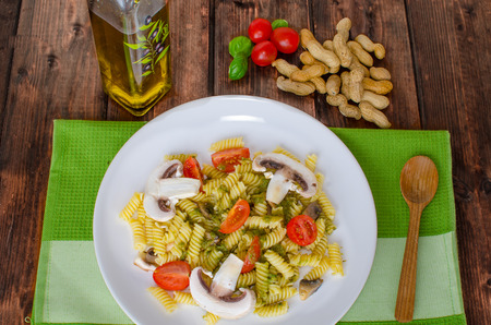 Pasta with basil pesto, nuts and mushrooms and tomato photo
