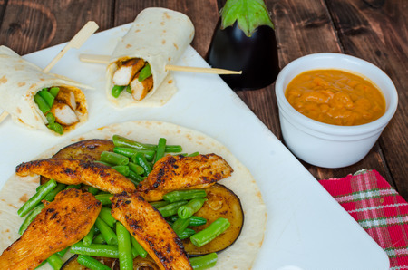 Chicken tortilla with beans and red curry on wood table photo