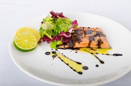 Salmon with a reduction of balsamic vinegar and sugar, fresh salad, lemon lime photo