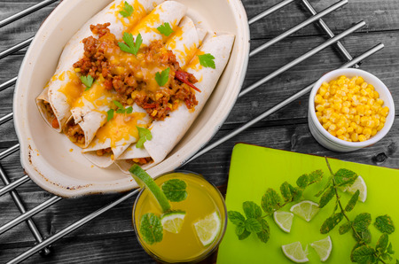 Baked meat tortilla with cheddar cheese, chilli peppers and corn, lime drink Imagens
