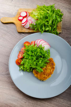 Breaded pork chops in Parmesan cheese, lettuce and radish and cherry tomatoes photo