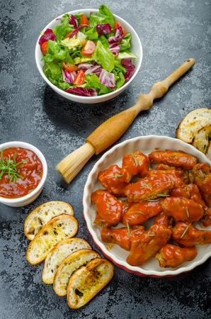 Hot chicken wings with spicy habanero sauce and mixed salad with cherry tomatoes, grilled baguette with olive oil photo
