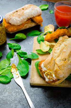 Schnitzel with spicy dip and spinach in a rustic baguette and homemade chips photo