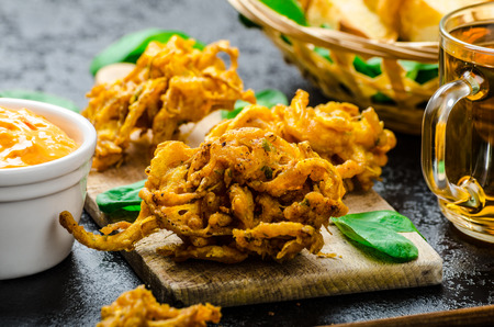 onion bhaji: Crispy Onion Bhajis with creame cheese dip with jalapeno and crunchi toast on spinach leaves and czech beer Stock Photo