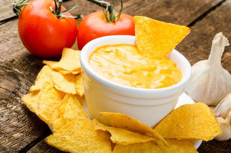 tortilla de maiz: Virutas de tortilla con tomate y queso de ajo chapuzón en la mesa de madera vieja