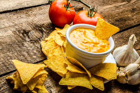 chips and salsa: Tortilla chips with tomato and cheese-garlic dip on wood old table