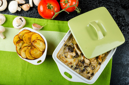 Baked chicken with mushrooms and cream, spicy potato chips baked in the oven photo
