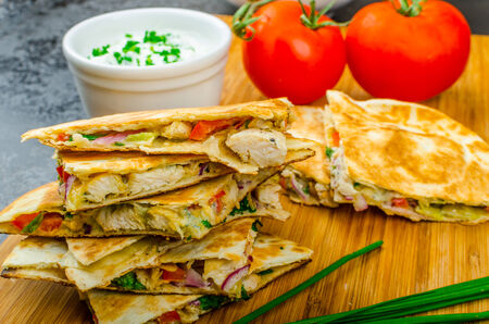 Chicken quesadilla with tomato, red onions, parsley and red pepper, fresh salad and creame sour-chive dip photo