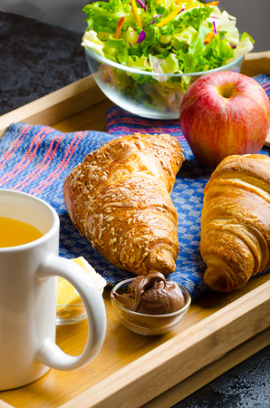 Breakfast in bed on wood tray - apple, croissant, butter, chocolate and salad