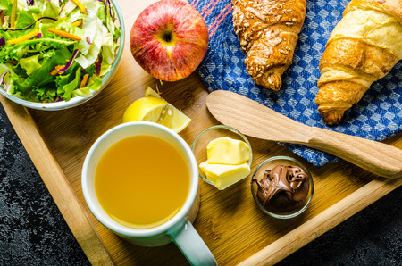 breakfasting: Breakfast in bed on wood tray - apple, croissant, butter, chocolate and salad