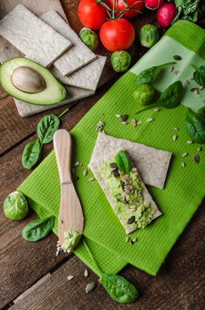Home avocado spread on Crispbread with seeds sunflower, pumpkin, sesame and herbs spinach photo