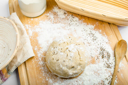 Making bread home in a basket - scuttle on white tablecloth photo