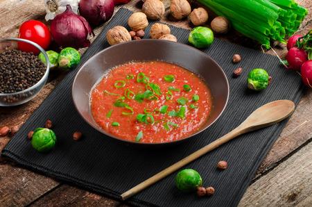 Hete salsa tomaat met lente-ui en rode peper op houten plaat met garnituur