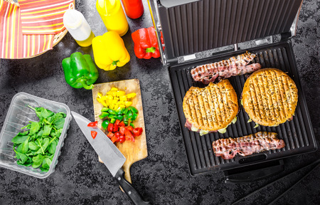 Panini make, panini shop, ketchup, mustard, olive oil bottle, herbs, napkins and vegetable prepare photo