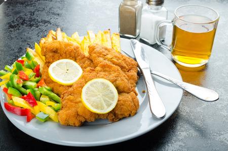 budvar: Schnitzel with french fries, homemade, platter, czech beer, vegetable, lemons Stock Photo