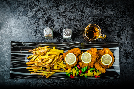 budvar: Schnitzel with french fries, homemade, platter, czech beer, vegetable, lemons Stock Photo