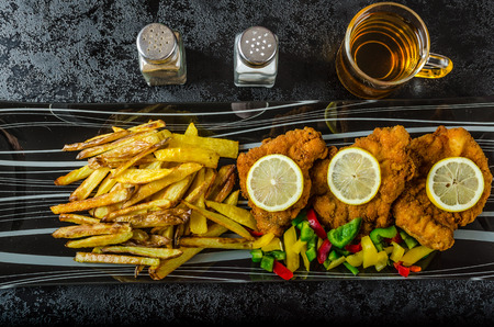 Schnitzel with french fries, homemade, platter, czech beer, vegetable, lemons 版權商用圖片