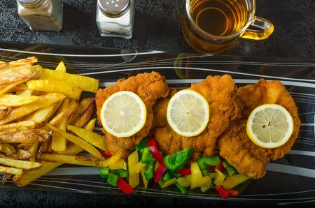 Schnitzel with french fries, homemade, platter, czech beer, vegetable, lemons photo