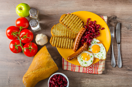 English breakfast - garlic toast, fried egg, beans and savory sausages photo