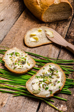 Homemade bread buttered with healthy seeds and herbs - chive photo