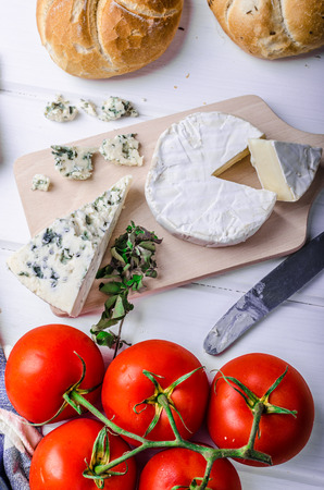 Gourmet cheeses - camembert and blue cheese on a cutting board, homemade pastries