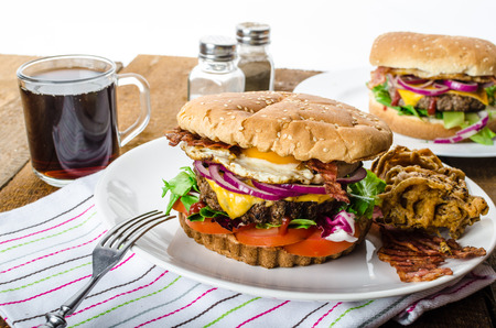Beef burger with red onion and fried egg, crispy bacon and salad. photo